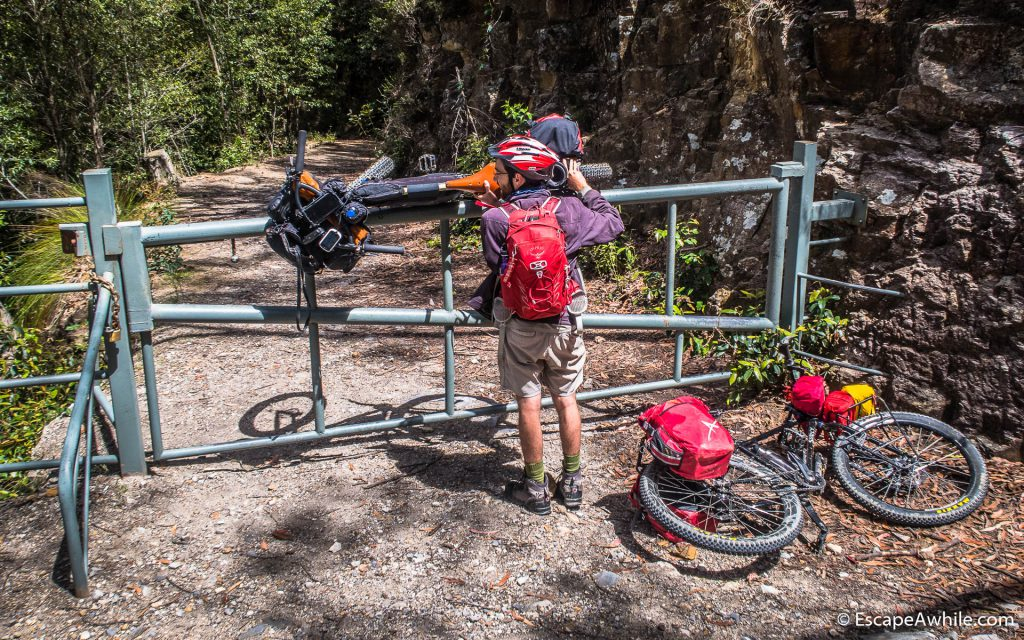 Wrestling bikes over the locked gates on the Griffiths fire trail